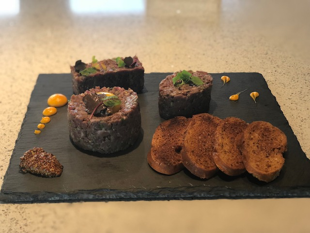 charcoal plate with tartare and toasted baguette