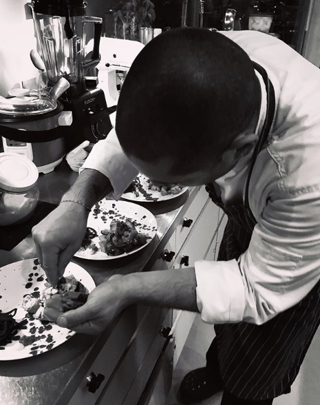 black and white photo of chef putting final touches on plates