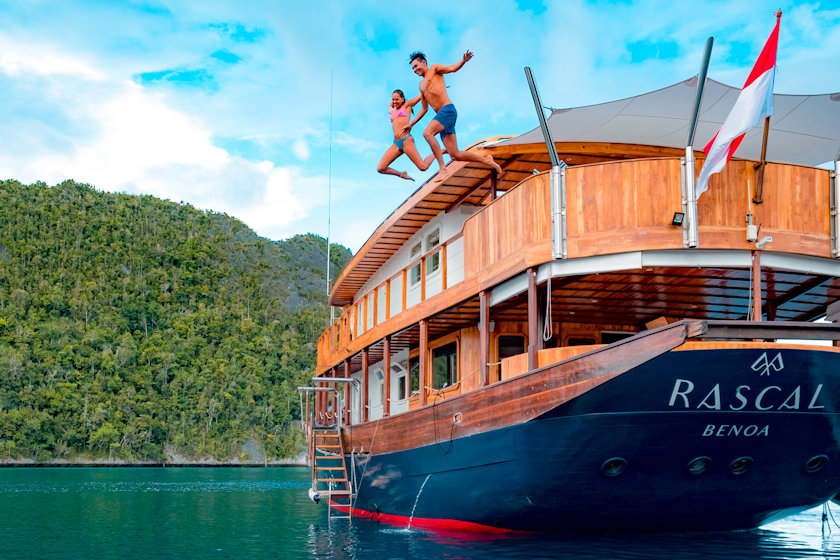 couple jumping off side of a wooden boat in Indonesia