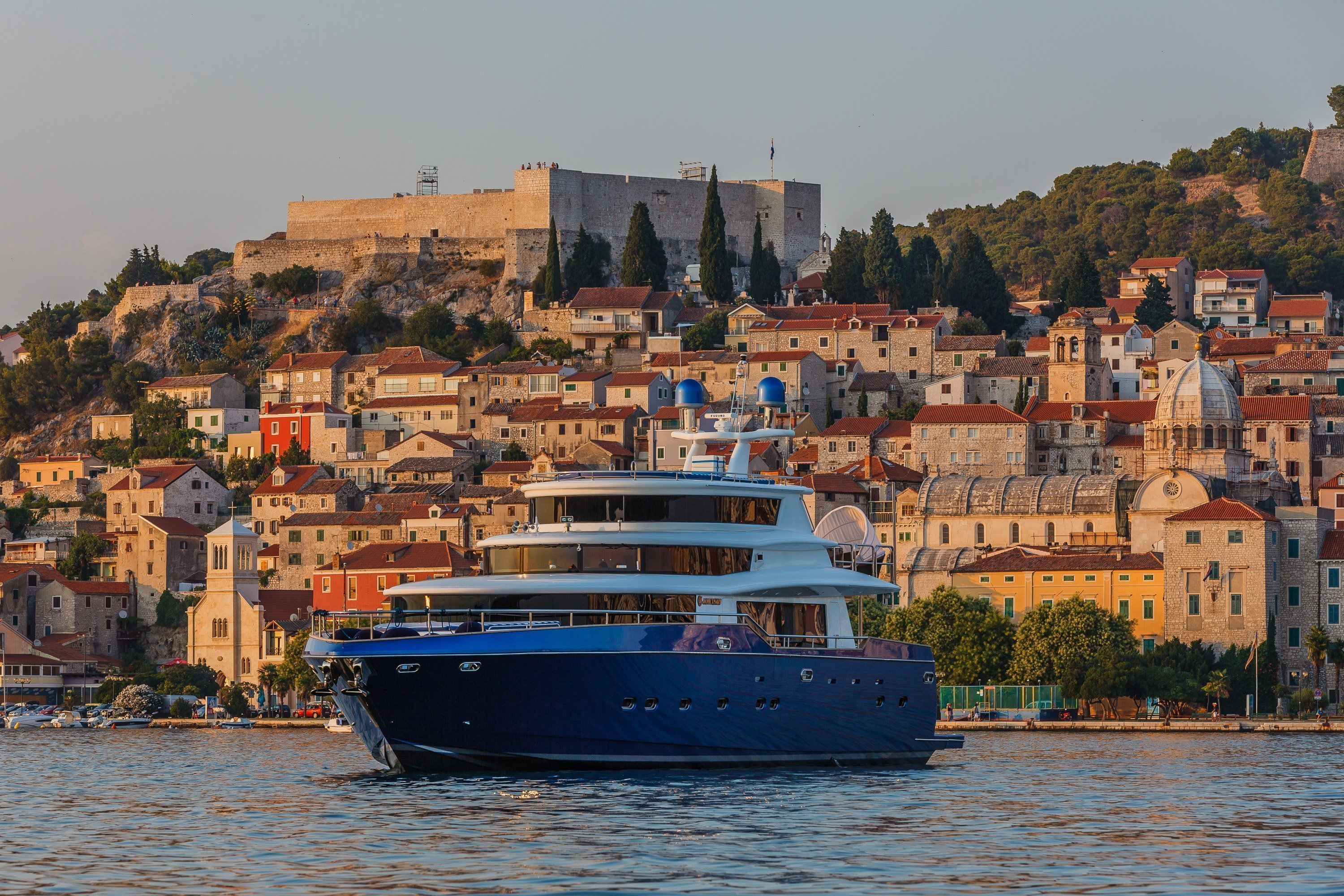 yacht with blue hull in front of Croatian hillside town