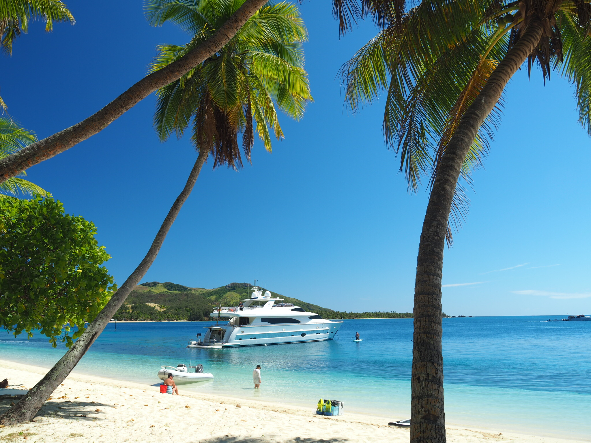 white yacht in the south Pacific in front of white sand beach