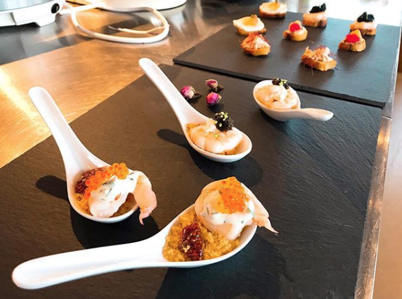 plated spoons with appetizers on charcoal trays
