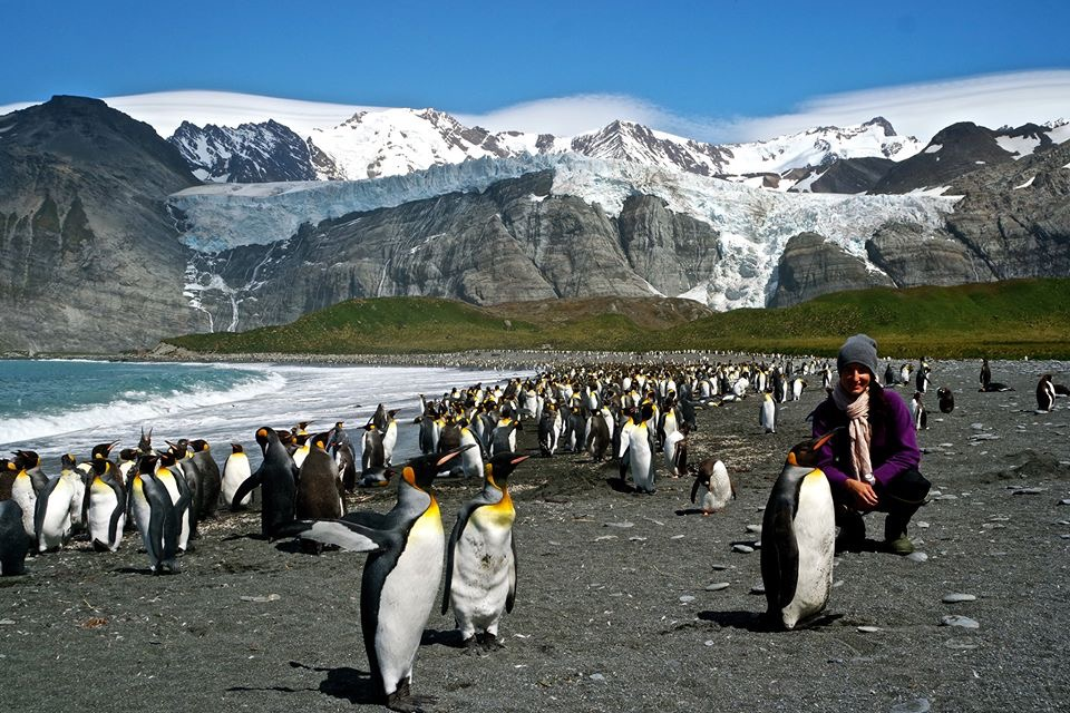 woman crouching on beach with penguins in Antarctica with snow capped mountains in background