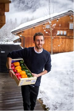 man walking along snow with fresh peppers and cabin in the background