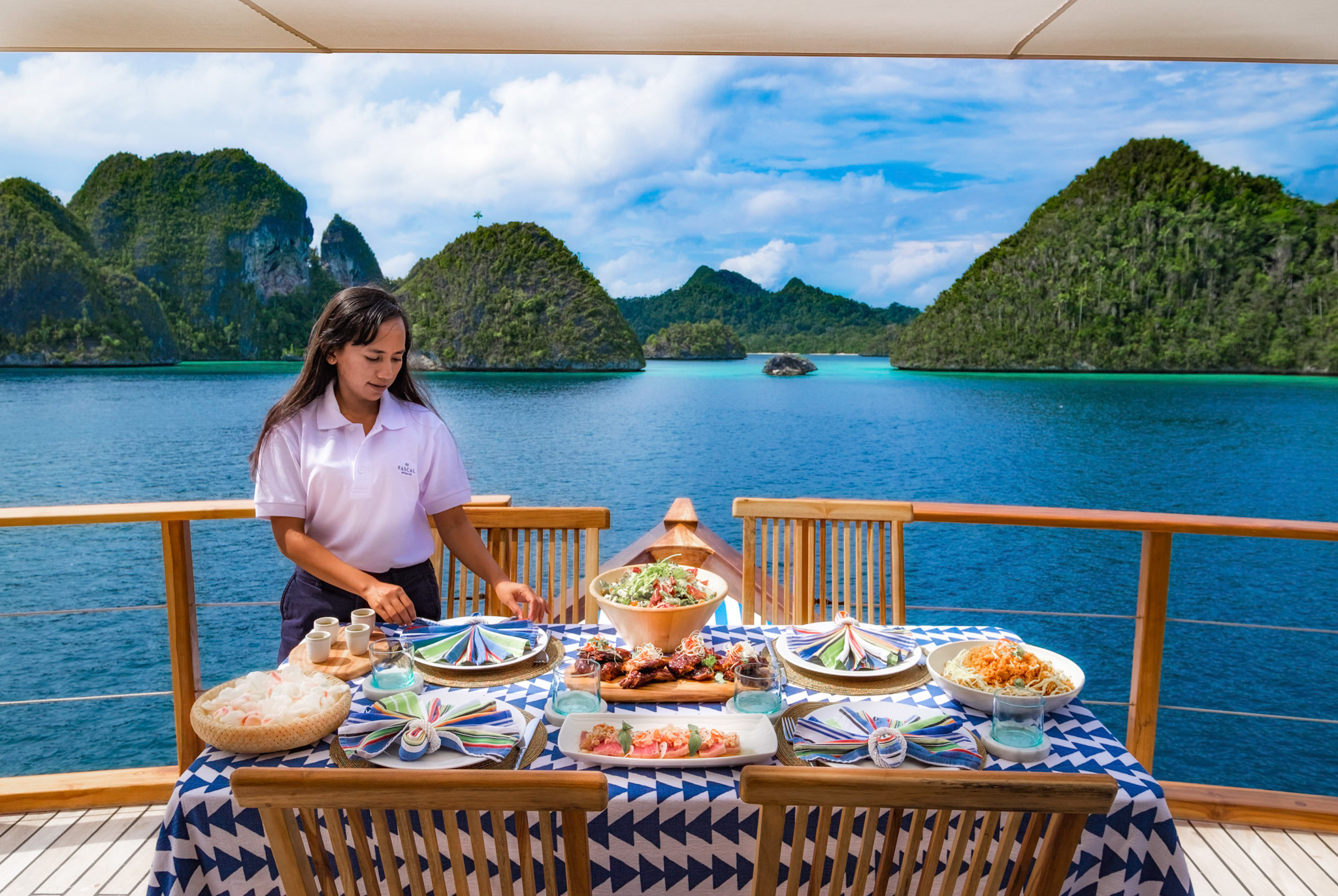 stewardess sets table on aft deck with Indonesian islands in background