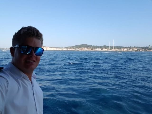 selfie of young male deckhand smiling with sea and coastline in background