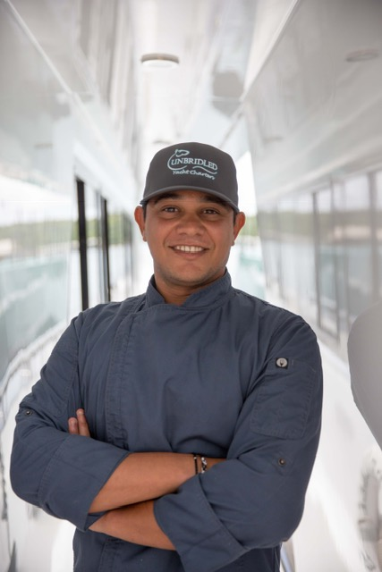 male chef smiling in uniform onboard yacht